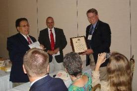 El Dr. Dale J. Pratt (a la derecha) de Brigham Young University al recibir el Premio José Martel. del Presidente Carrillo (izquierda) y el Secretario Del Mastro (centro) durante la Asamblea Trienal.