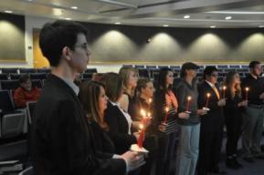 Los neófitos con las velas encendidas durante la iniciación.