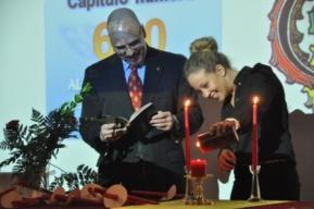 La Presidenta Capitular enciende la madre vela de Alpha Alpha Alpha durante la instalación del capítulo 600 mientras el Dr. Mark P. Del Mastro, Director Ejecutivo, observa.